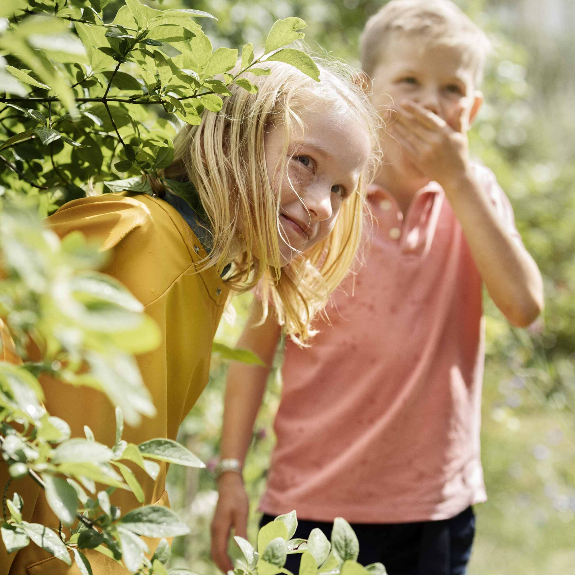 Two kids hiding in the bushes